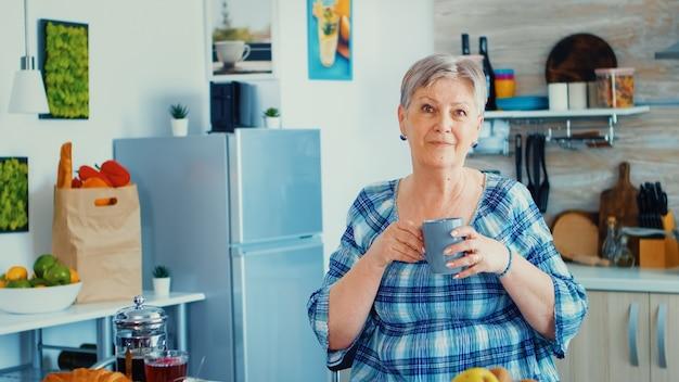 Grootmoeder die tijdens het ontbijt een kop warme koffie voor het aanrecht in de keuken neemt en met een glimlach naar de camera kijkt. authentiek portret van ontspannen oudere oudere in de ochtend, genietend van vers warm