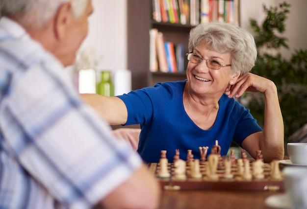 Grootmoeder en grootvader schaken ter ontspanning