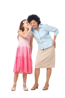 Grootmoeder en haar kleindochter fluisteren iets in haar oor, van volle lengte
