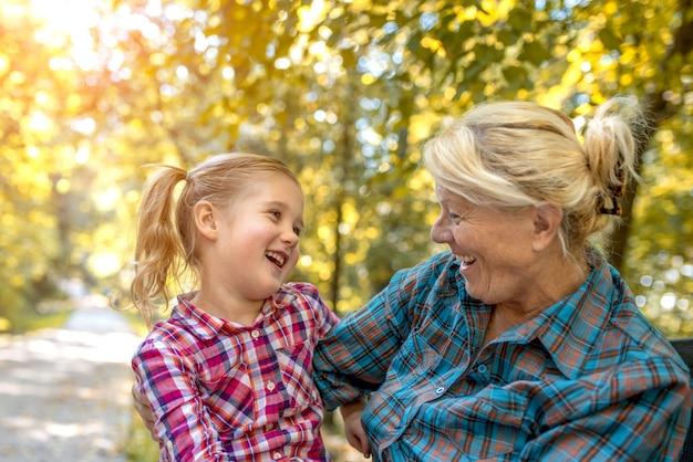 Grootmoeder en haar schattige kleindochter kijken elkaar aan en lachen in een park