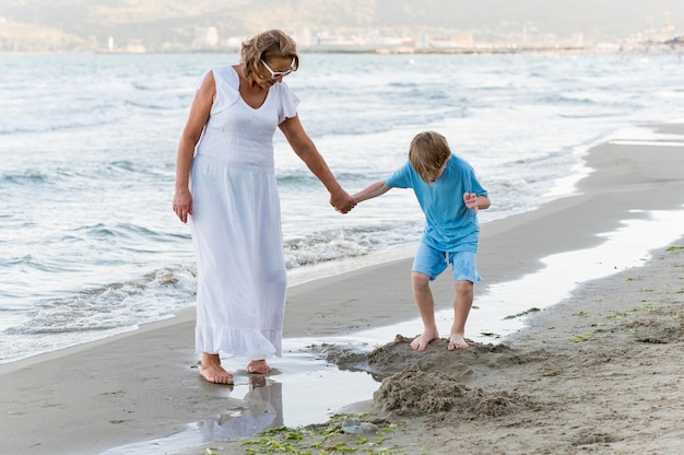 Grootmoeder en jongen die op strand lopen