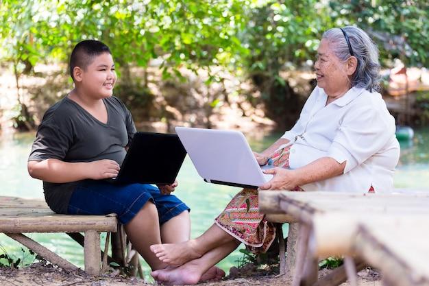 Grootmoeder en jongen genieten met laptop