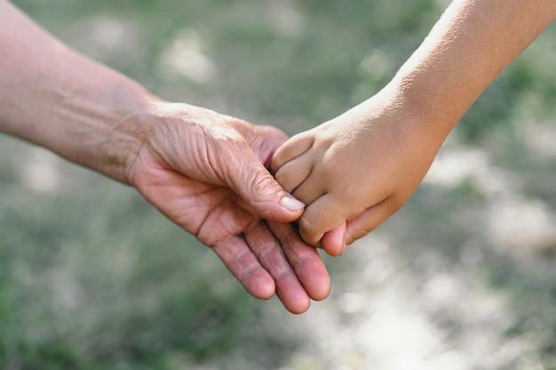 Grootmoeder en kind houden elkaars hand vast