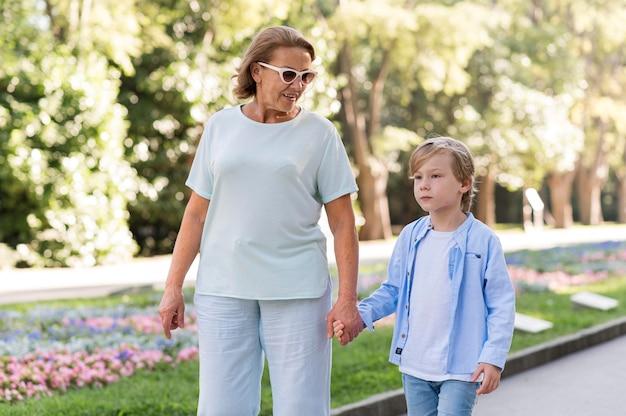 Grootmoeder en kind wandelen in het park