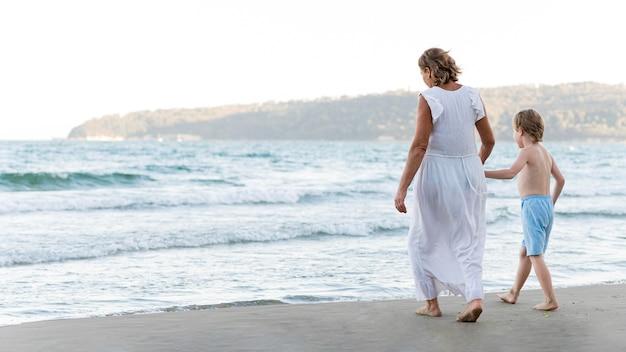 Grootmoeder en kind wandelen op het strand