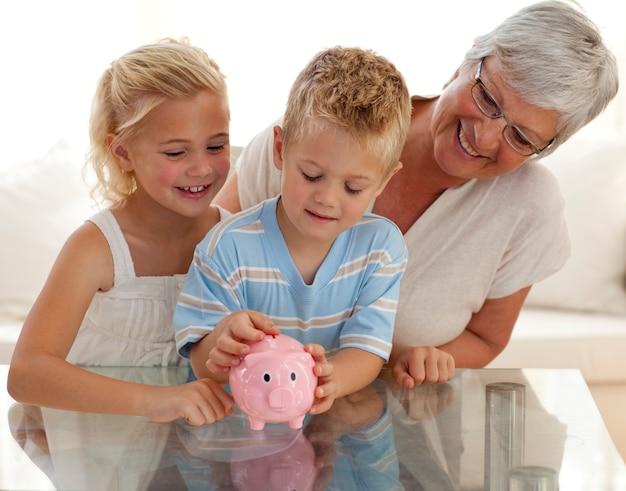 Grootmoeder en kinderen die geld besparen in een spaarpot