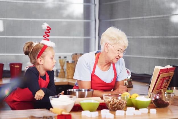 Grootmoeder en kleindochter bereiden kerstcake