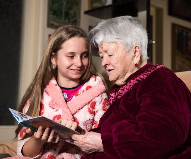 Grootmoeder en kleindochter die thuis een boek lezen