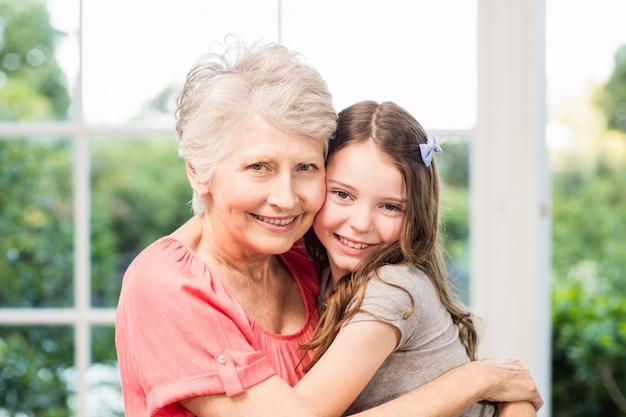Grootmoeder en kleindochter die thuis omhelzen