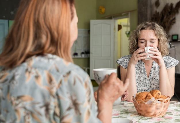 Grootmoeder en kleindochter drinken koffie tijdens het ontbijt