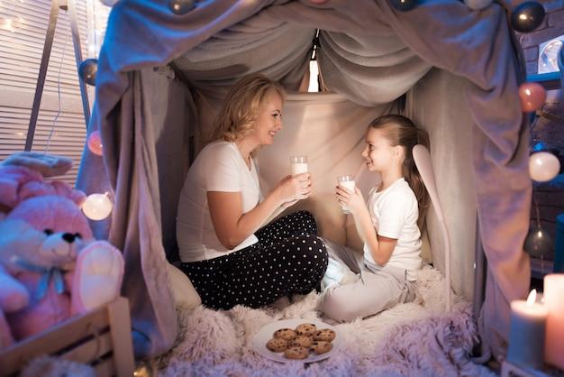 Grootmoeder en kleindochter eten koekjes met melk.