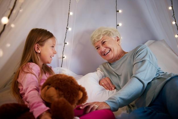 Grootmoeder en kleindochter genieten in slaapkamer