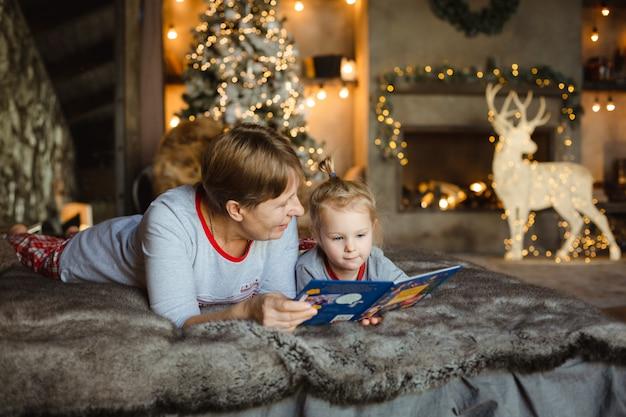 Grootmoeder en kleindochter in kerstmispyjama's die een boek lezen.