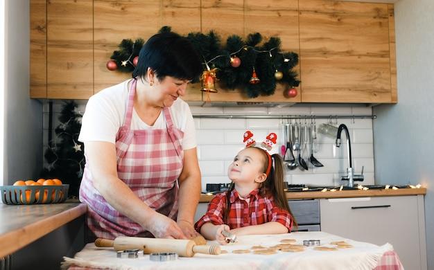 Grootmoeder en kleindochter kijken elkaar aan terwijl ze koekjes bakken in de keuken in scandinavische stijl