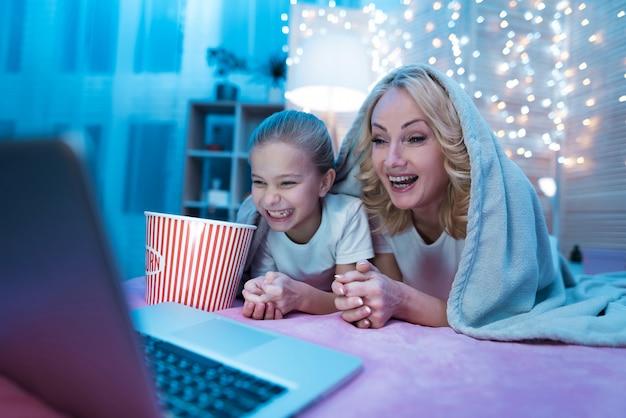 Grootmoeder en kleindochter kijken film op laptop.