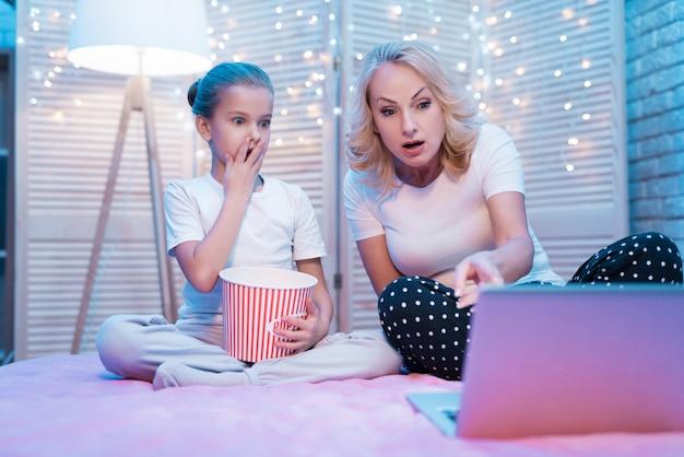 Grootmoeder en kleindochter kijken 's nachts naar een film