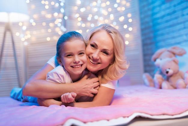 Grootmoeder en kleindochter knuffelen op bed