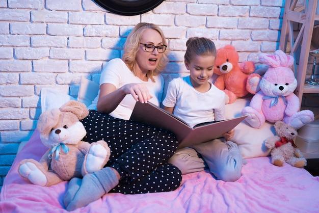 Grootmoeder en kleindochter lezen samen boek.