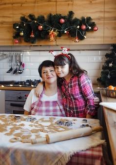 Grootmoeder en kleindochter omhelzen elkaar teder in de keuken in scandinavische stijl