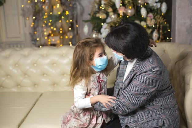 Grootmoeder en kleindochter op de bank in de woonkamer met kerstdecor knuffelen in medische maskers op hun gezichten. een gezinsvakantie tijdens het uitbreken van coronavirus en ziekte. nieuwjaar