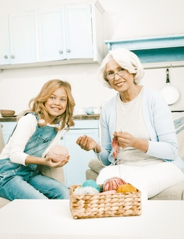 Grootmoeder en kleindochter poseren terwijl ze breien