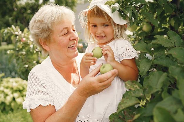 Grootmoeder en kleindochter samen, knuffelend en vrolijk lachend in een bloeiende abrikozentuin in april. familie buitenshuis levensstijl.