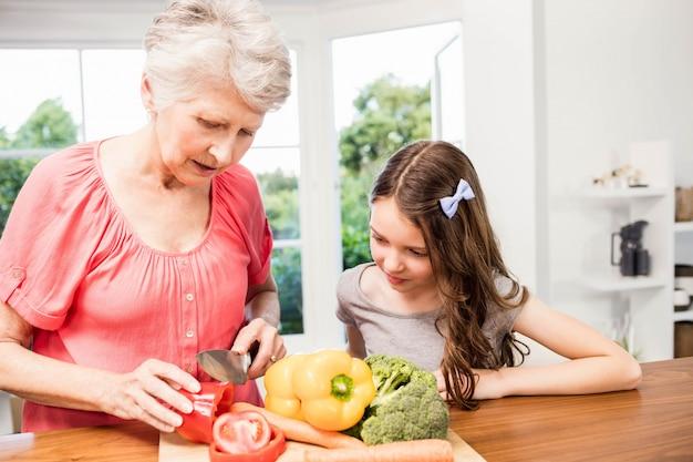 Grootmoeder en kleindochter snijdende groenten in de keuken