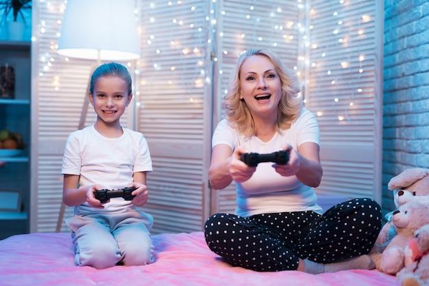 Grootmoeder en kleindochter spelen videogames.