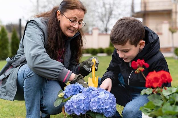 Grootmoeder en kleine jongen die in de tuin werken