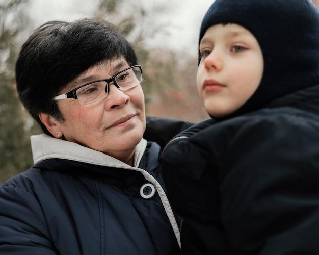 Grootmoeder en kleinzoon buiten in de winter