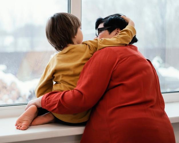 Grootmoeder en kleinzoon kijken samen door het raam