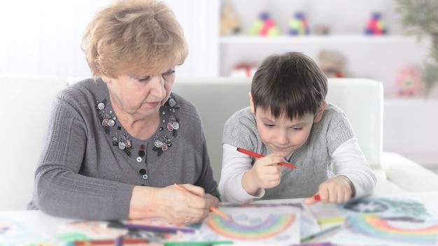 Grootmoeder en kleinzoon schilderen een regenboog in de kinderkamer