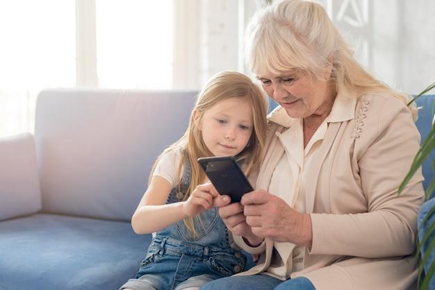 Grootmoeder en meisje mobiel gebruiken