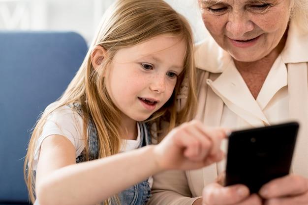 Grootmoeder en meisje mobiel kijken