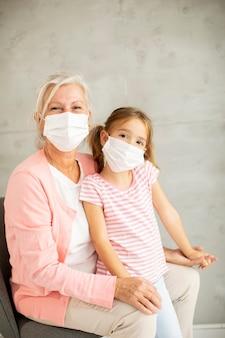 Grootmoeder en schattige kleine kleindochter die een ademhalingsmasker dragen