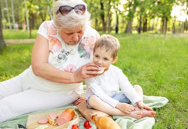 Grootmoeder en schattige kleinzoon lunchen samen op zomergras