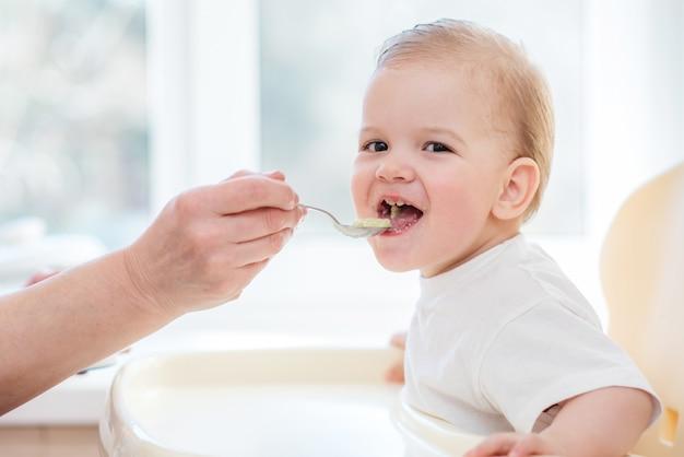 Grootmoeder geeft babyvoeding uit een lepel