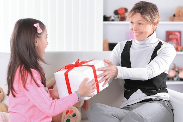 Grootmoeder geeft kleindochter een doos met een geschenk.