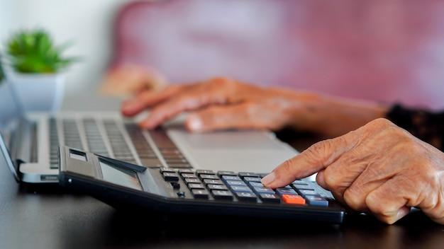 Grootmoeder hand druk op rekenmachine voor het tellen over maandelijkse kosten