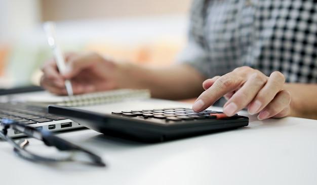 Grootmoeder hand druk op rekenmachine voor telling over maandelijkse kosten