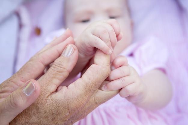 Grootmoeder handen met baby handen