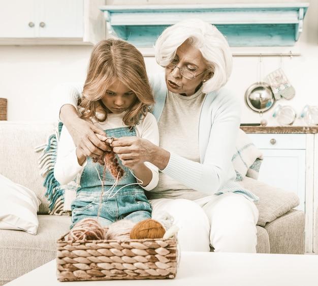 Grootmoeder helpen haar kleindochter breien