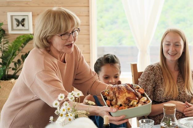 Grootmoeder in bril met kalkoen met aardappelen voor het avondeten voor haar familie