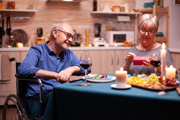 Grootmoeder kijkt naar cadeau van gehandicapte man in rolstoel. gelukkig vrolijk bejaarde echtpaar dat samen thuis eet, van de maaltijd geniet, hun huwelijk viert.