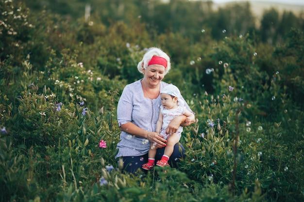 Grootmoeder knuffelen kleindochter in de natuur in zonnige zomerdag