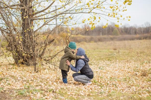 Grootmoeder knuffelen litlle kleinzoon buiten in herfst bos