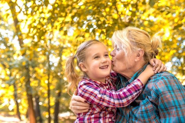 Grootmoeder kuste haar glimlachende vrouwelijke kleinkind in het park