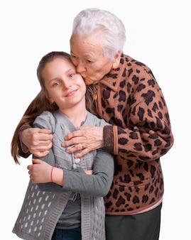Grootmoeder kuste haar kleindochter op een witte achtergrond