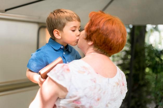 Grootmoeder kuste haar kleinzoon buiten