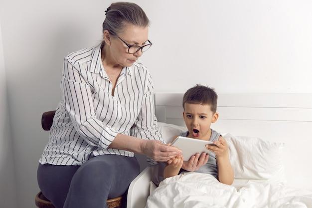 Grootmoeder met een bril en een wit overhemd leest een tablet voor aan haar kleinzoon liggend op het bed in een witte kinderkamer